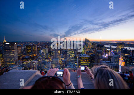 USA, New York State, New York City, Women photographing Manhattan at dusk - Stock Photo