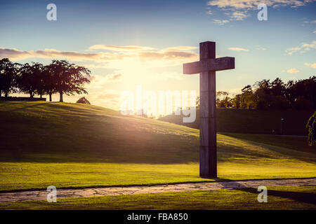 Sweden, Sodermanland, Stockholm, Gamla Enskede, Skogskyrkogarden, Cross in green valley at sunset - Stock Photo