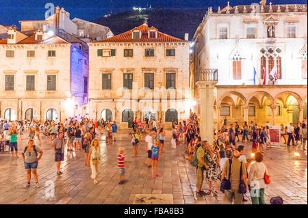 Tourists walk along Stradun, Placa or promenade which is the main street in the Old City of Dubrovnik,Dalmatia,Croatia, - Stock Photo