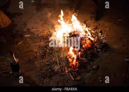 Fire built out of spent fireworks by homeless to keep warm, Berlin New Years Eve 2013 - Stock Photo