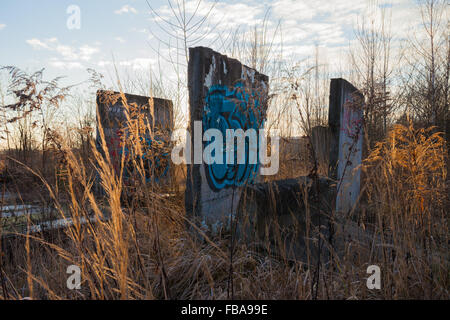 Abandoned concrete structures covered with graffiti at dawn - Stock Photo