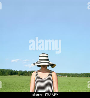 Finland, Uusimaa, Lapinjarvi, Woman wearing hat covering her face - Stock Photo