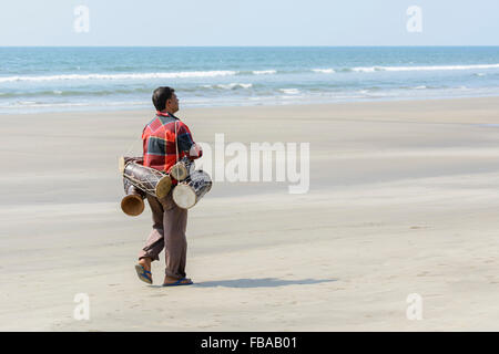 An Indian man selling traditional hand drums walks along an empty beach, Mandrem beach, North Goa, India - Stock Photo