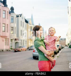 Finland, Uusimaa, Helsinki, Portrait of mother holding daughter (2-3) on street - Stock Photo