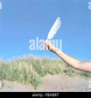 Finland, Pori, Yyteri, Close-up of woman's hand with feather on beach - Stock Photo