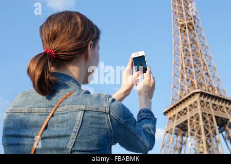 France, Ile-de-France, Paris, Rear view of woman taking picture of Eiffel Tower - Stock Photo