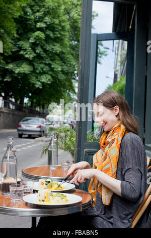 France, Ile-de-France, Paris, Young woman by table in sidewalk cafe - Stock Photo