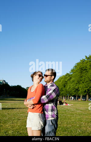 Finland, Uusimaa, Helsinki, Kaivopuisto, Young couple embracing in park - Stock Photo