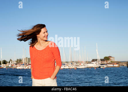 Finland, Uusimaa, Helsinki, Kaivopuisto, Portrait of smiling young woman with sea in background - Stock Photo