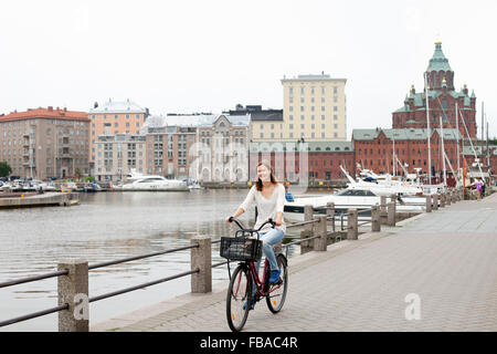 Finland, Uusimaa, Helsinki, Kruunuhaka, Young woman riding bicycle in city - Stock Photo
