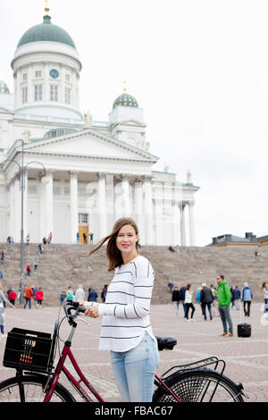 Finland, Uusimaa, Helsinki, Senaatintori, Young woman with bicycle with Lutheran Cathedral in background - Stock Photo