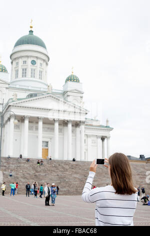 Finland, Uusimaa, Helsinki, Senaatintori, Young woman photographing Lutheran Cathedral - Stock Photo
