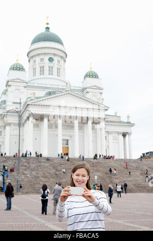 Finland, Uusimaa, Helsinki, Senaatintori, Young woman photographing self with Lutheran Cathedral in background - Stock Photo
