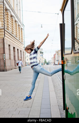 Finland, Uusimaa, Helsinki, Kruunuhaka, Young woman jumping out of tram - Stock Photo