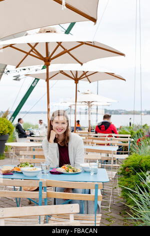 Finland, Uusimaa, Helsinki, Kaivopuisto, Portrait of smiling young woman in open air restaurant - Stock Photo