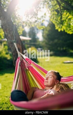 Finland, Heinola, Paijat-Hame, Woman embracing girl (4-5) in hammock - Stock Photo