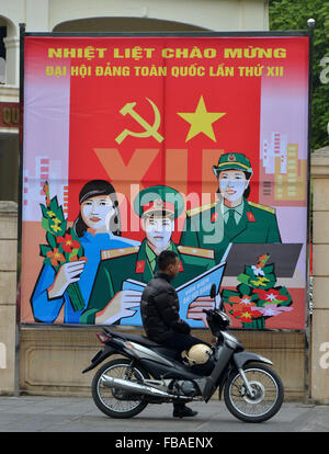 Hanoi, Vietnam. 13th Jan, 2016. A man parks his motorbike near a propaganda poster to welcome the 12th National - Stock Photo