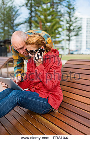 Australia, Queensland, Woman and man in park using digital table - Stock Photo