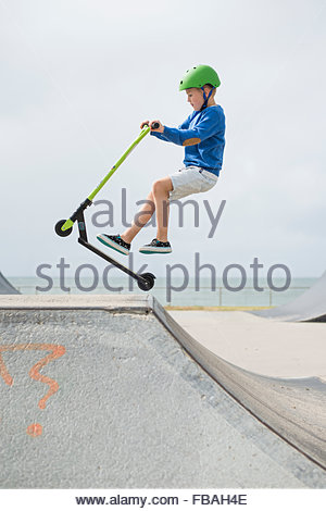 Australia, Queensland, Mooloolaba, Young boy (6-7) jumping on ramp on push scooter - Stock Photo