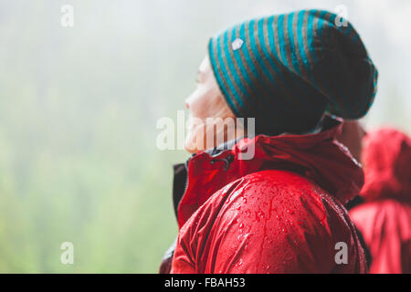 Switzerland, Ausserferrera, Young woman wearing warm red jacket and woolly hat - Stock Photo