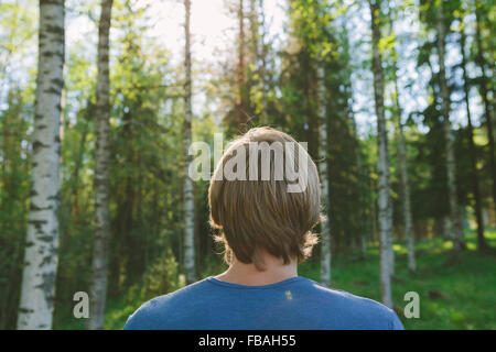 Finland, Mellersta Finland, Jyvaskyla, Saakoski, Young man looking at forest - Stock Photo