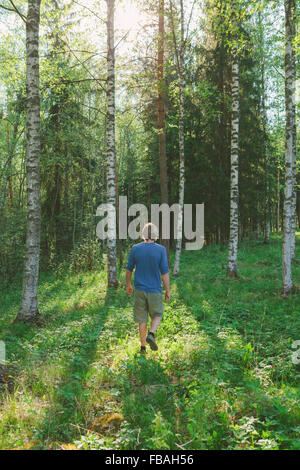 Finland, Mellersta Finland, Jyvaskyla, Saakoski, Young man walking across forest glade - Stock Photo