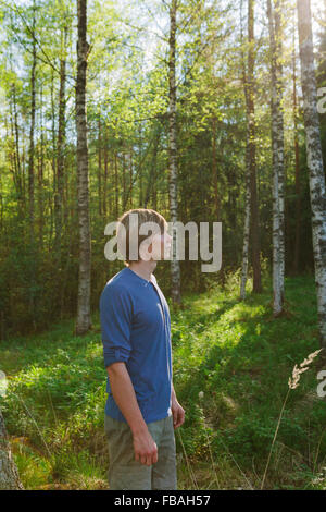 Finland, Mellersta Finland, Jyvaskyla, Saakoski, Portrait of young man standing in forest - Stock Photo