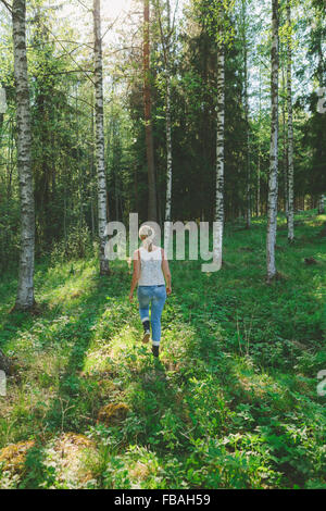 Finland, Mellersta Finland, Jyvaskyla, Saakoski, Woman walking across forest glade - Stock Photo