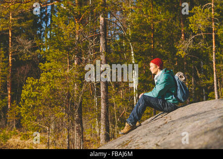 Finland, Esbo, Kvarntrask, Young man sitting on stone surface in forest - Stock Photo
