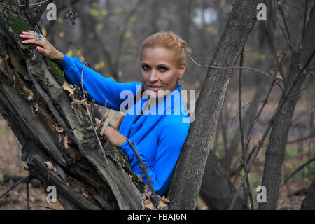 Portrait of beautiful young woman in blue dress standing in a forest framed by tree branches - Stock Photo
