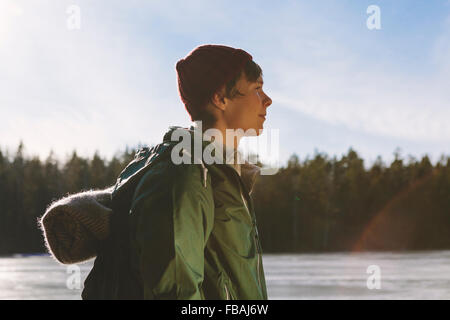 Finland, Esbo, Kvarntrask, Portrait of young man on shore of forest lake - Stock Photo