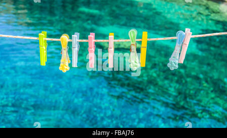 Colorful clothes pegs on a rope - Stock Photo