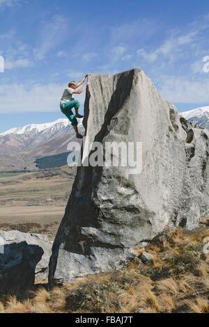 New Zealand, Castle Hill, Young man climbing up steep rockface - Stock Photo