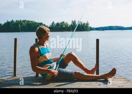 Finland, Pirkanmaa, Salmentaka, Lake Palkanevesi, Young man fishing off lake pier - Stock Photo