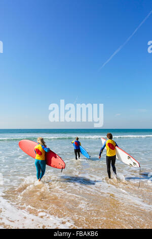 Portugal, Lisbon, Three people carrying surfboards - Stock Photo