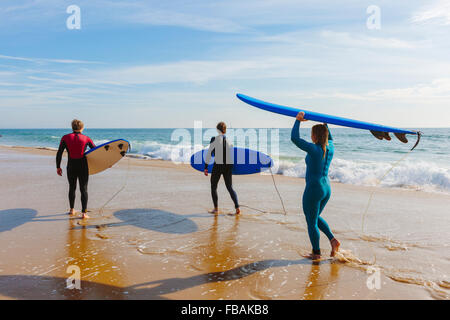 Portugal, Lisbon, Three people carrying surfboards on beach - Stock Photo