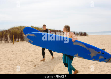 Portugal, Lisbon, Two people carrying surfboards on beach