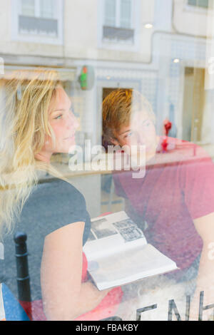 Portugal, Lisbon, Two people looking through window