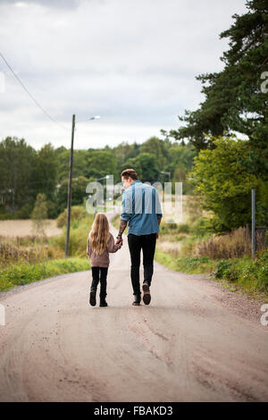Finland, Uusimaa, Raasepori, Karjaa, Father walking with daughter (6-7) along country road - Stock Photo