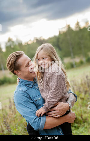Finland, Uusimaa, Raasepori, Karjaa, Father holding his daughter (6-7) - Stock Photo