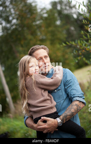 Finland, Uusimaa, Raasepori, Karjaa, Father with his daughter (6-7) looking at view - Stock Photo