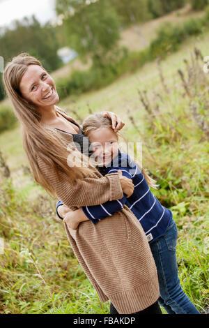 Finland, Uusimaa, Raasepori, Karjaa, Mother hugging her daughter (6-7) - Stock Photo