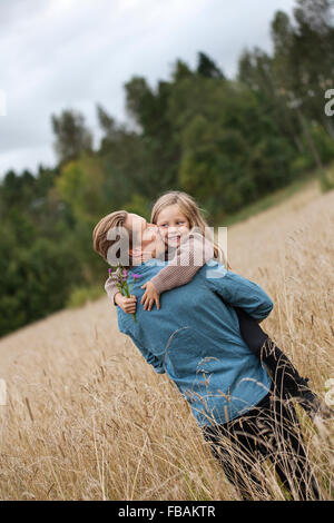 Finland, Uusimaa, Raasepori, Karjaa, Father kissing his daughter (6-7) on cheek - Stock Photo