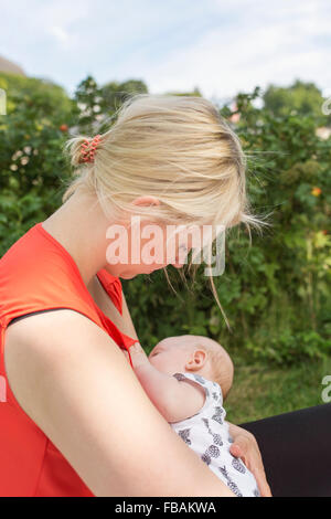 Finland, Mother holding and breastfeeding newborn son (0-1 months) - Stock Photo