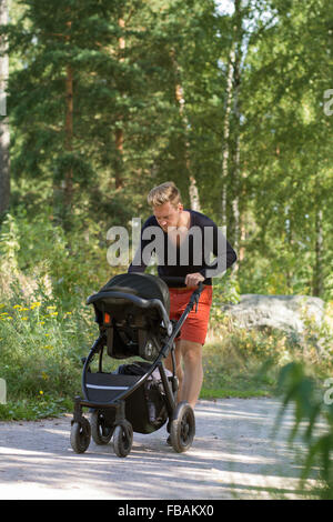 Finland, Uusimaa, Father walking with baby boy (0-1 months) in stroller - Stock Photo
