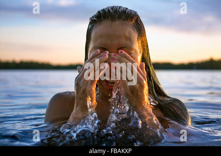 Finland, Pohjanmaa, Luoto, Young woman coming out of water - Stock Photo