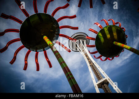 The landmark Space Needle soars overhead with two colorful flower sculptures. - Stock Photo