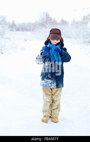 Finland, Keski-Suomi, Aanekoski, Young boy (6-7) standing in snowy meadow and adjusting scarf - Stock Photo