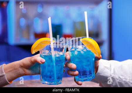 The hands with alcohol cocktails making toast on a blue bar background - Stock Photo