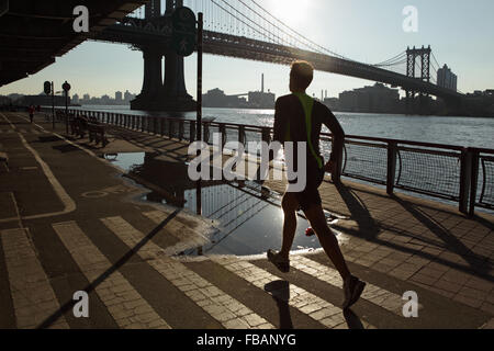 Man running along the East River Esplanade with the Manhattan Bridge in the background as the sun rises - Stock Photo